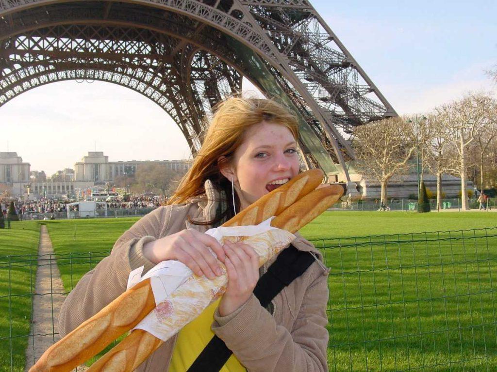 Девушка с багетом на фоне Эйфелевой башни
